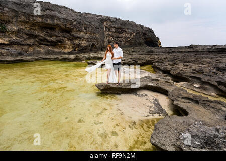 A young girl and a guy near the sea, surrounded by rocks. The water in the pool has an unusual yellow color. - Stock Photo