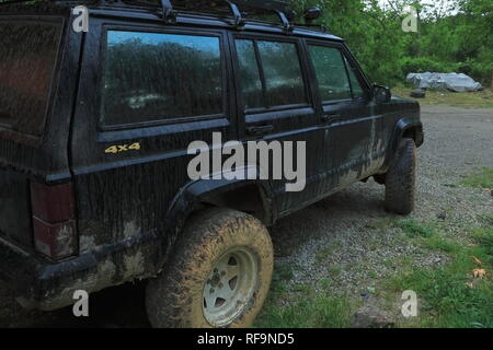 Muddy 4x4 off-road car. A black jeep taking a break at an off-road competition in the woods in Sapanca. Turkey. - Stock Photo