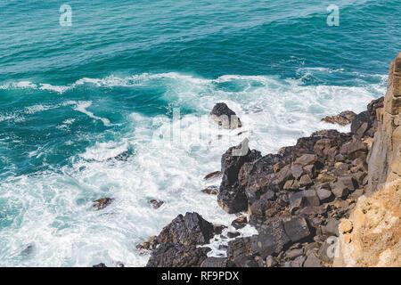 Sun shining down on splashing rocks - Stock Photo