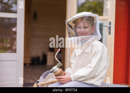 Portrait of a 7 year old girl with beekeeper suit for protection from the bees. In her hand she holds a beekeeper's pipe - Stock Photo