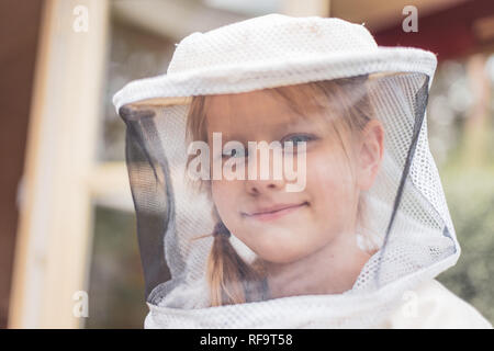 Portrait of a 7 year old girl with beekeeper suit for protection from the bees - Stock Photo