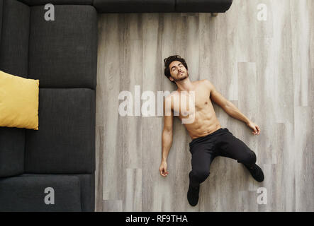 Muscular young good looking white male taking a nap on floor tired after working out at his house. Shirtless exhausted fitness instructor sleeping wit - Stock Photo