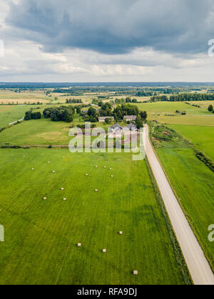 Aerial Photo of old Farmer houses with Road by its Side and Agriculture Fields Around it in Early Spring on Sunny Day - Concept of Peaceful Life in Co - Stock Photo