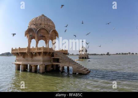 Artistically carved temples and shrines around The Lake Gadisar Jaisalmer. - Stock Photo