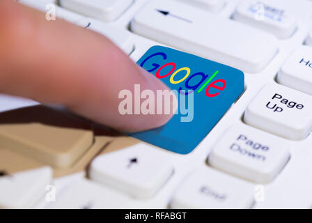 Finger pressing a Google button on a PC computer keyboard. - Stock Photo
