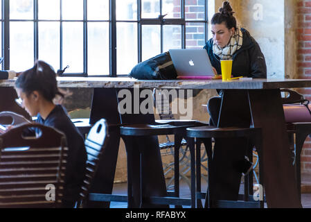 Woman with laptop computer in the Central Food Hall at Ponce City Market in Atlanta, Georgia. (USA) - Stock Photo