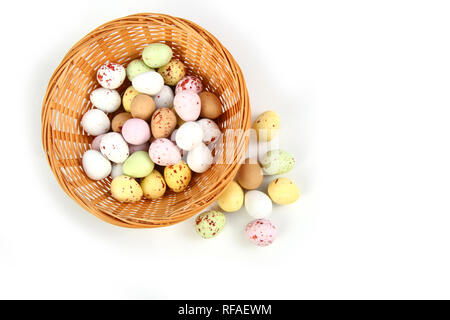Chocolate mini Easter eggs in straw or whicker basket against a white background - Stock Photo