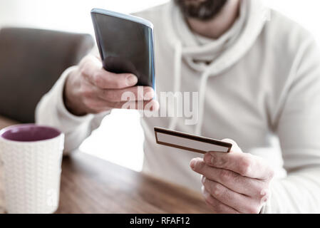 man entering credit card information on smartphone - Stock Photo