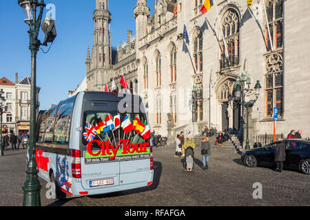 City Tour's minibus for guided sightseeing trip in front of the Provinciaal Hof / Province Court on the market place in Bruges, West Flanders, Belgium - Stock Photo