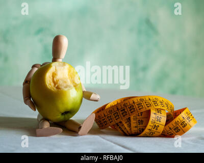A wooden figurine with a bitten green apple and a tape measure, on top of a table - Stock Photo