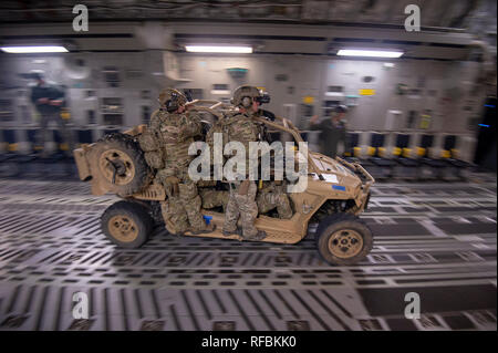 Soldiers with 2-20th Special Forces Group (Airborne) as well as other members of the special operations community conduct a high-speed combat offloading of their vehicles from a C-17 Globemaster during a mock nighttime assault on the Grenada Dam in Grenada, Mississippi January 20, 2019. The exercise involved a simultaneous assault from multiple points, with the intent of gaining control over an insurgent-held dam.    Southern Strike 2019 is a large-scale, joint multinational combat exercise that provides tactical level training for the full spectrum of conflict. It emphasizes air dominance, ma - Stock Photo