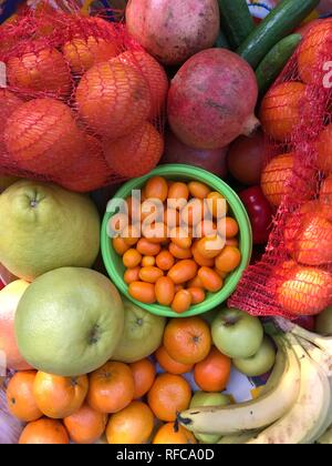 Fruits background colorful flat lay image of bananas, pomegranates, and citrus fruits. Flat lay top view Eat healthy vitamins concept. - Stock Photo