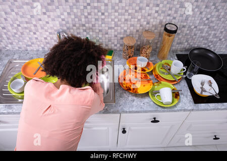 Tired Young Woman Leaning Near Sink With Dirty Colorful Utensils In The Kitchen - Stock Photo