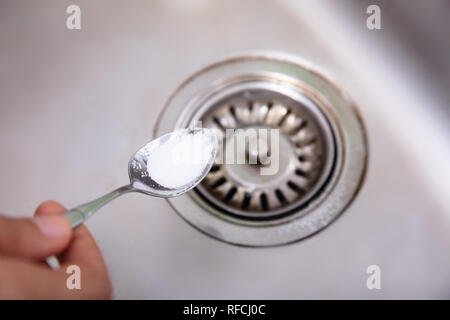 A Person Putting The Baking Soda With Spoon On Drain In The Washbasin - Stock Photo