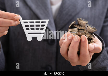 Close-up Of Businesswoman's Hand Showing Pile Of Coins Against Shopping Cart - Stock Photo