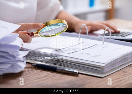 Close-up Of A Businesswoman's Hand Holding Magnifying Glass Over Invoice At Workplace - Stock Photo