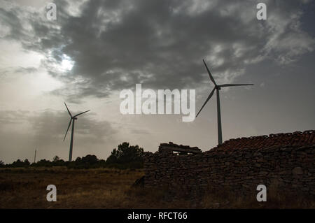 Two windmills near an old house with cloudy sky at countryside - Stock Photo