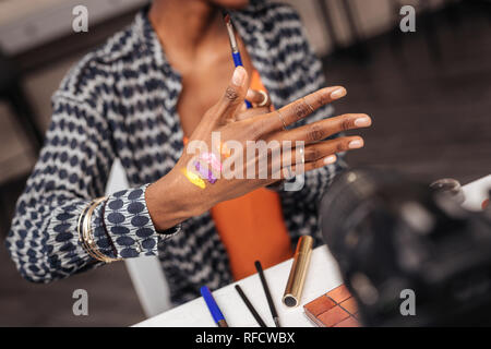 New colors. Dark-skinned african american woman wearing a gold bracelet showing new swatches - Stock Photo