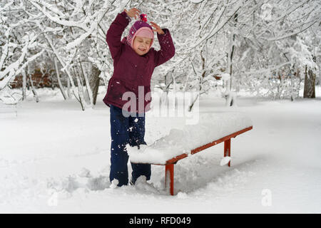 Little cute girl in winter outdoors. She throws snow up. Girl rejoices and fools - Stock Photo