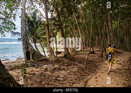 A photo of a woman and son walking on a hiking trail close to a beautiful beach with turquoise blue water at Manzanillo National Park, Costa Rica - Stock Photo