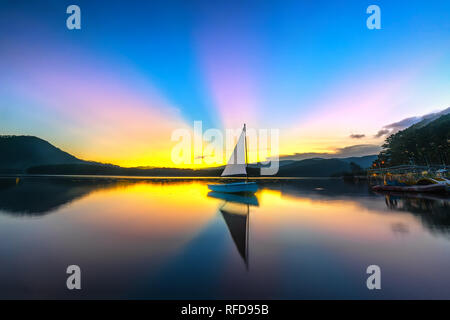 Lonely sailboat in the lake during beautiful sunset with sun rays clouds shines from sky colorful reflecting off the mystical lake to end the day - Stock Photo