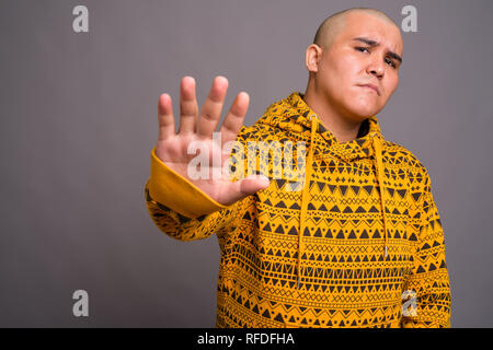 Young bald Asian man against gray background - Stock Photo