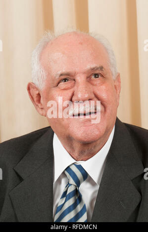 Happy old man in suit looking up smiling - Stock Photo