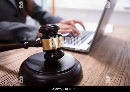 Close-up Of Judge Mallet And Gavel In Front Of Man Using Laptop On Wooden Desk - Stock Photo