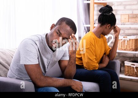 Young Depressed African Couple Sitting On Sofa - Stock Photo