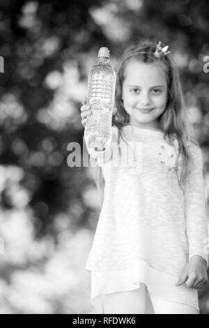 Water bottle in hand of small child on blurred natural background. Girl princess hold fresh water. Thirst and dehydration. Refreshment and freshness. Childhood and childcare, black and white. - Stock Photo