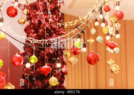 Colorful red, gold, green and silver Hanging Glittering ball baubles background with decorated red Christmas Tree in shopping mall. Special Holiday, F - Stock Photo