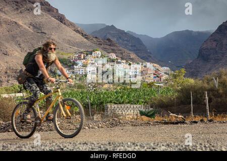 Spain, Canary islands, La Gomera. Valle Gran Rey. Banana plantation and village La Calera. Cyclist - Stock Photo