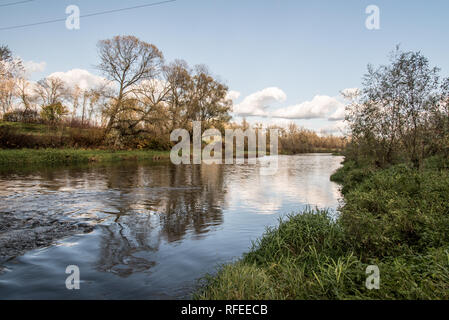 Olse river near its junction with Stonavka river near Karvina city in Czech republic during nice autumn day with blue sky and few clouds - Stock Photo