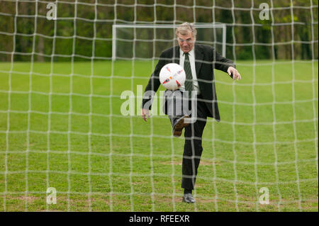 Former England footballer Trevor Brooking  international West Ham MBE kicking a football towards a net like taking  penalty kick. - Stock Photo