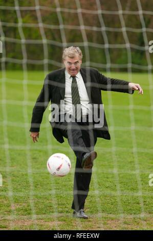 Former England footballer Trevor Brooking  international West Ham MBE kicking a football towards a net like taking  penalty kick. - Stock Photo