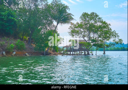 The silhouette of old nipa hut on wooden stilts among the mangrove trees on Kangy river, Chaung Tha zone, Myanmar. - Stock Photo