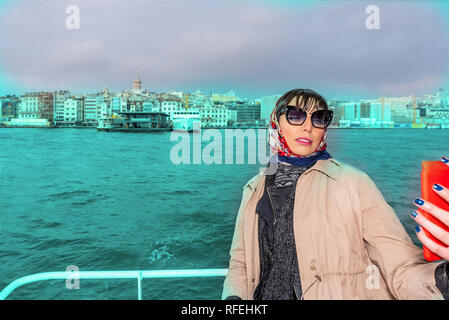 Beautiful woman take selfies while cruising in ferry with view of Galata Tower at background in Istanbul,Turkey - Stock Photo