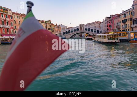 Rialto Bridge (Ponte de Rialto) across Grand Canal at sunrise / sunset time with Italian flag, Venice, Italy - Stock Photo