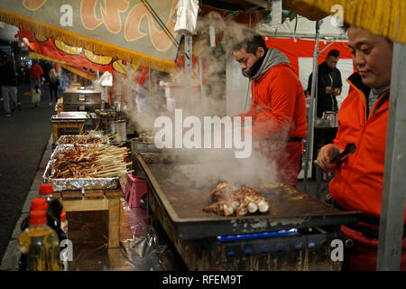 Fried cuttlefish sellers on a stall during Hatsumode or New Year at Ikuta Shrine in Kobe, Japan - Stock Photo