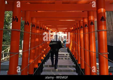 Man walking through Torii at the Shinto Ikuta Shrine during Hatsumode or New Year in Kobe, Japan - Stock Photo