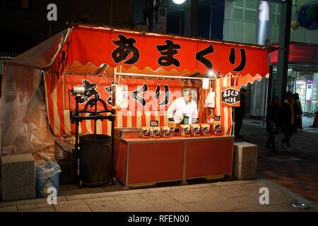 Roast chestnut street seller stall during Hatsumode or New Year at Ikuta Shrine in Kobe Japan - Stock Photo