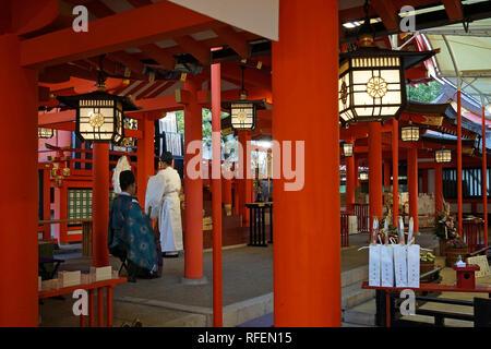 Shinto priests at Ikuta Shrine during Hatsumode or New Year in Kobe, Japan - Stock Photo