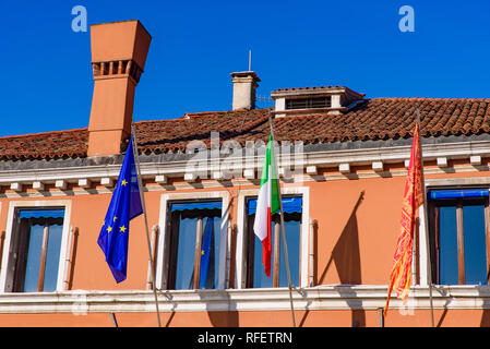A building with flags of European Union, Italy, and Venice - Stock Photo
