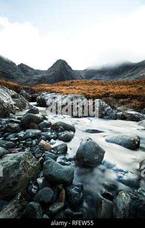 Long exposure of river stream with colourful stones in front of fog covered mountain range at the Fairy Pools (Isle of Skye, Scotland, Europe) - Stock Photo