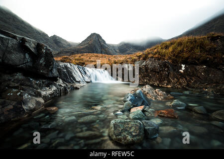 Picturesque waterfall with clear water and colourful stones in front of fog covered mountain range at the Fairy Pools (Isle of Skye, Scotland, Europe) - Stock Photo