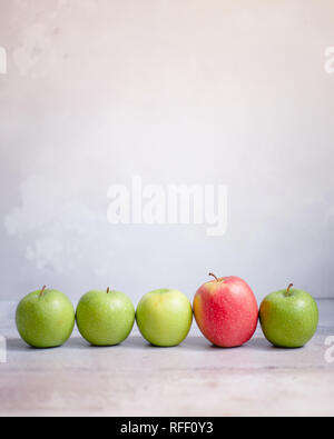 Four green apples and one red apple in a line against a neutral background - Stock Photo