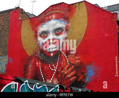Aboriginal face on red background of graffiti, Spear St, Northern Quarter, Manchester, England, UK - Stock Photo