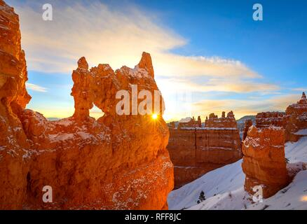 Sun star shining through hole in bizarre rock formation in morning light, snowy rock landscape with Hoodoos in winter - Stock Photo