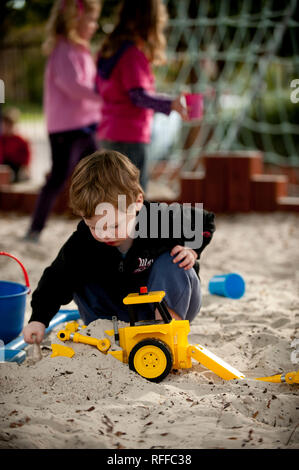 Toddler playing in a sand pit - Stock Photo