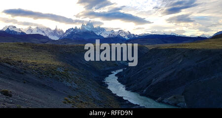 View of Fitz Roy and Rio De Las Vueltas canyon near El Chalten, Patagonia, Argentina. The lights of the sunset on the peak of the Mount Fitzroy - Stock Photo